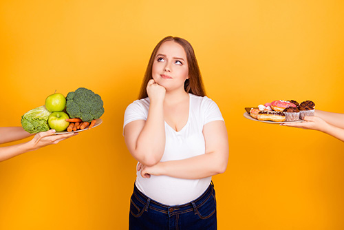 Female choosing between healthy and unhealthy food